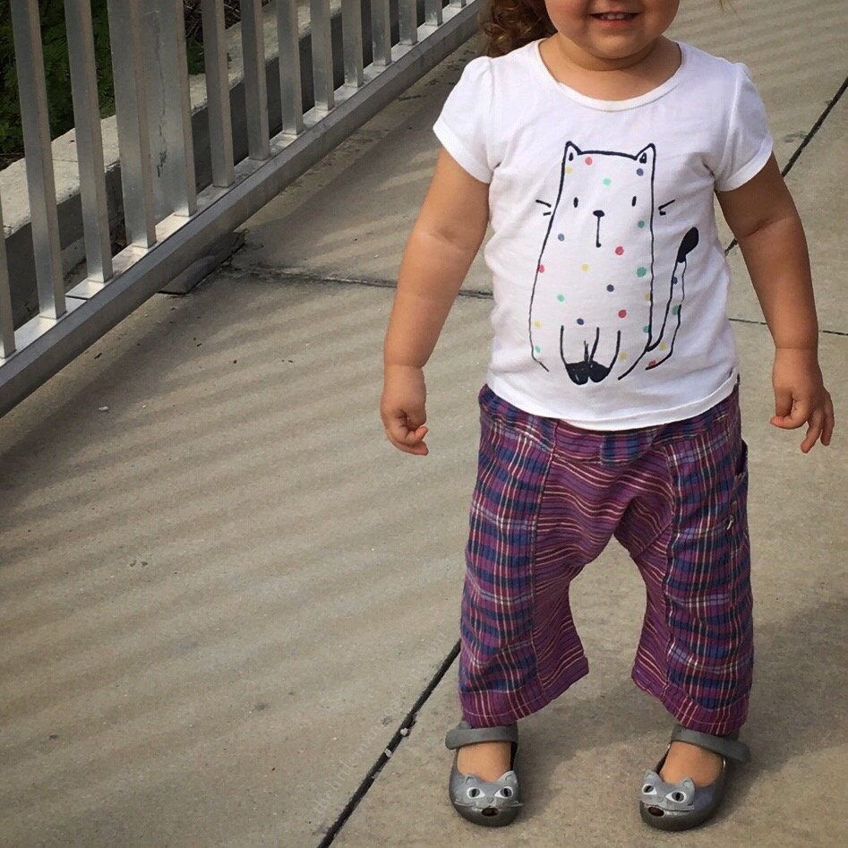 Toddler girl wearing cat shaped shoes and a t-shirt depicting a cat