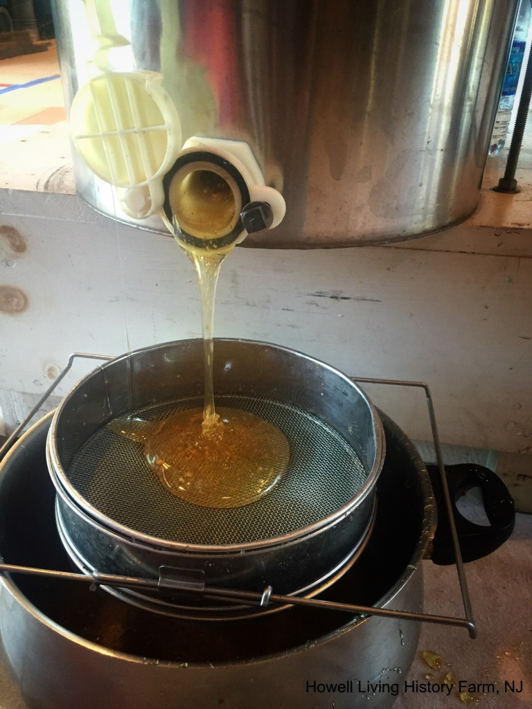 Golden honey dripping out of a metal centrifuge device