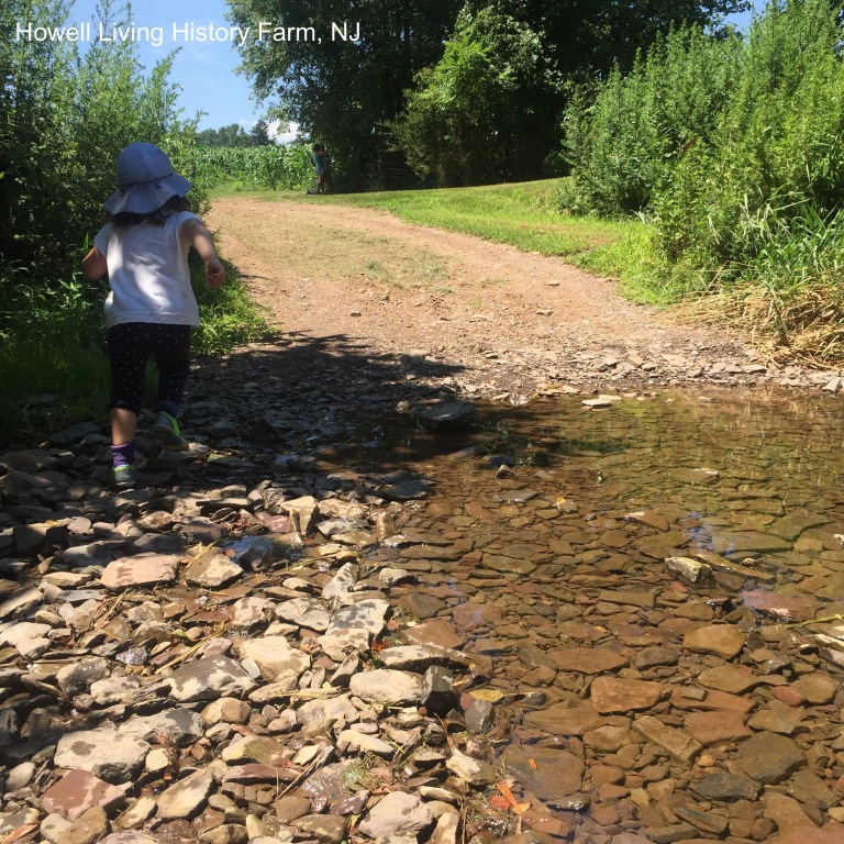 Child running on pebbles by a creek