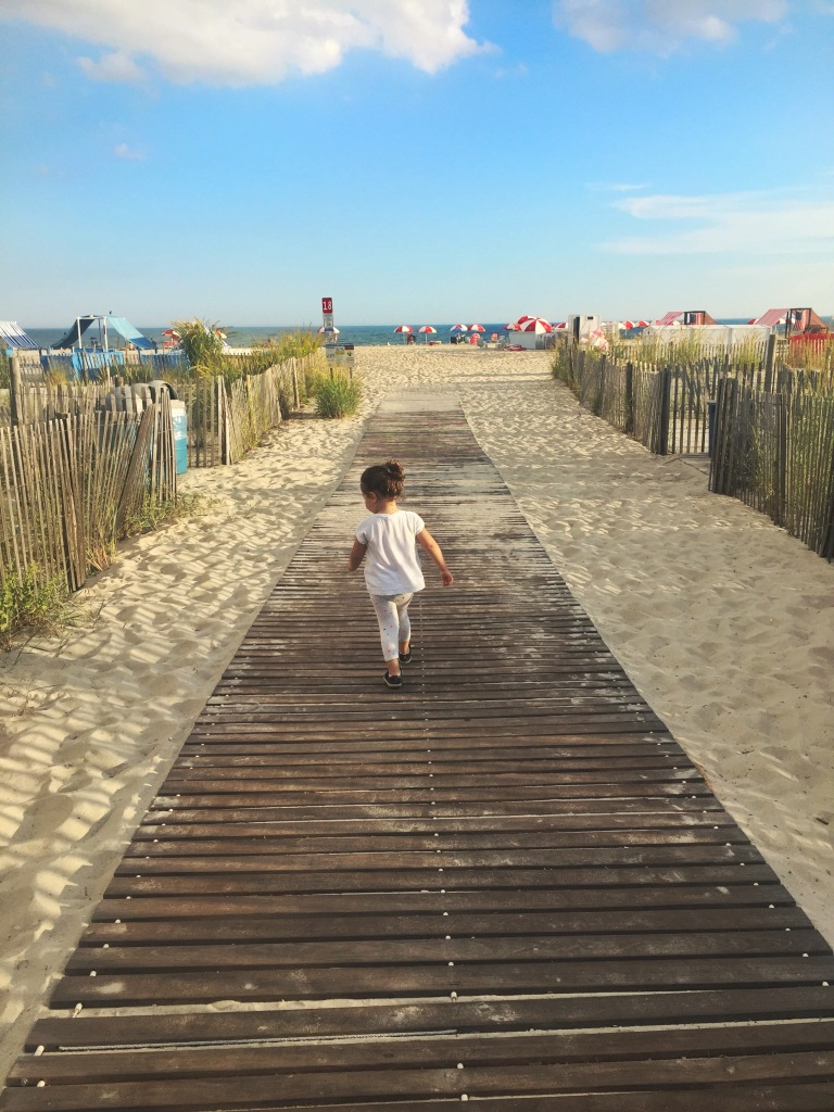 Young child walks towards the sea